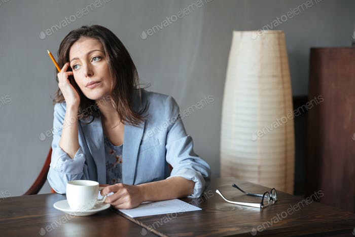 Thinking serious woman writer sitting indoors