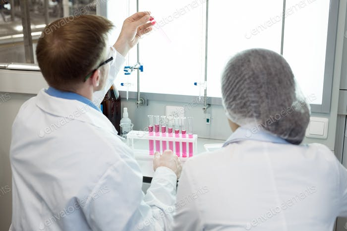 Microbiologists studying pink solution in test tube