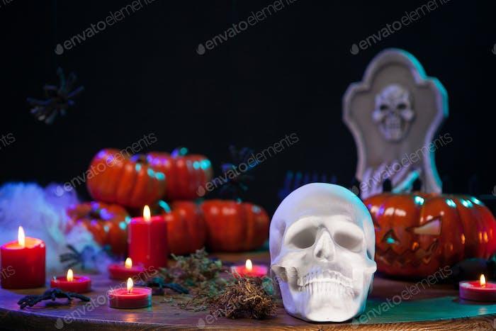 Gruseliger menschlicher Schädel mit gruseligem Kürbis hinten auf Holztisch für Halloween-Feier