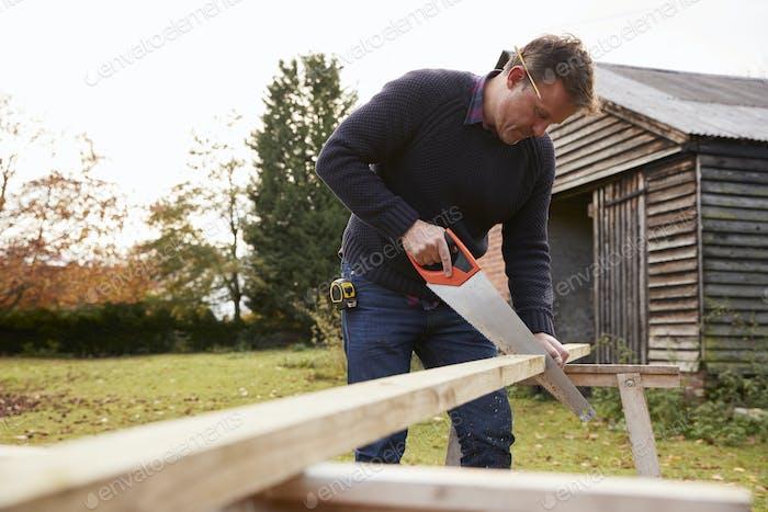 Mature Man Sawing Wood Outdoors