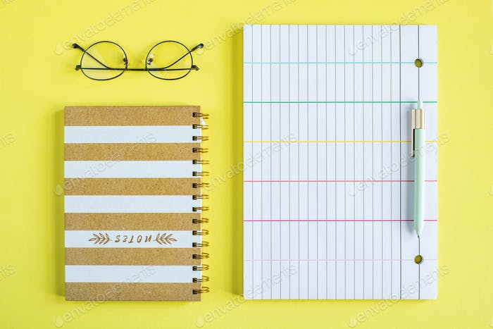 Eyeglasses, closed notebook with spiral binder, pen and lined paper