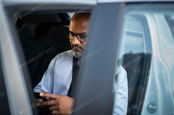 Mature african businessman using smartphone in car