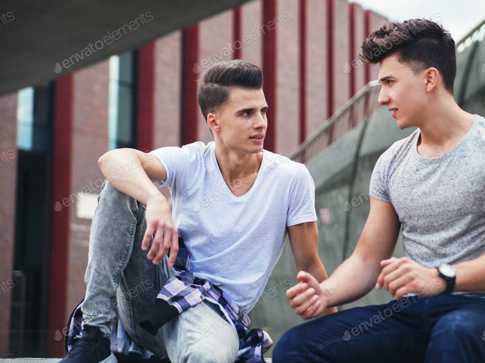 Two friends sitting in the city and talking