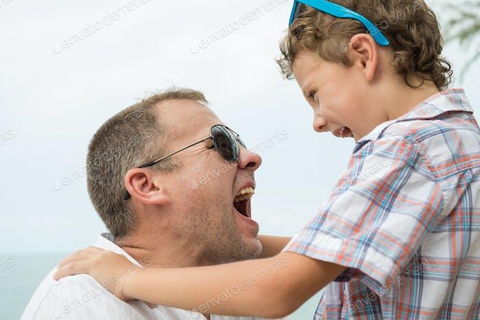 Vater und Sohn spielen am Strand zur Tageszeit.
