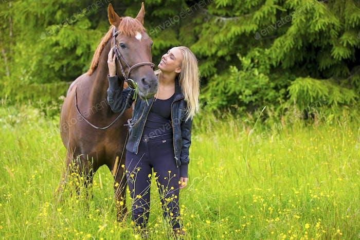Mujer joven con su caballo árabe de pie en el campo
