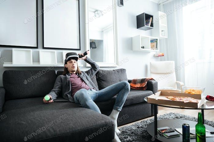 Konzentrierter Mann sitzt zu Hause drinnen spielen Spiele