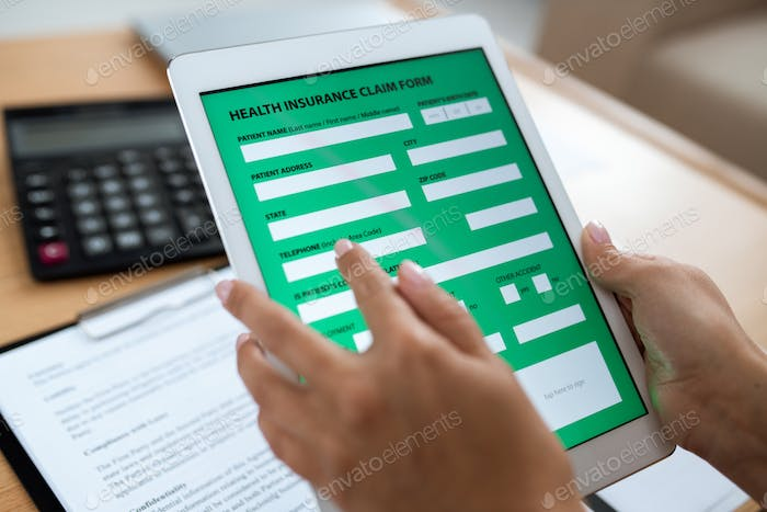 Electronic form of health insurance in digital tablet held by human hands
