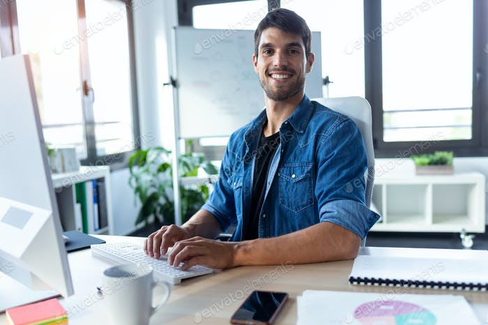 Software developer looking at camera while working with computer in the modern startup office.