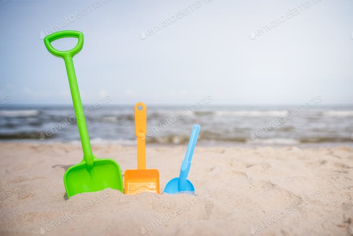 Three colorful toy shovels on the beach