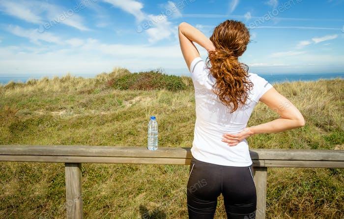 Sportliche Frau berührt durch Verletzung die Nacken- und Rückenmuskulatur