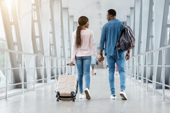 Romantisches schwarzes Paar Zu Fuß Mit Koffern In Flughafenterminal, Hände halten