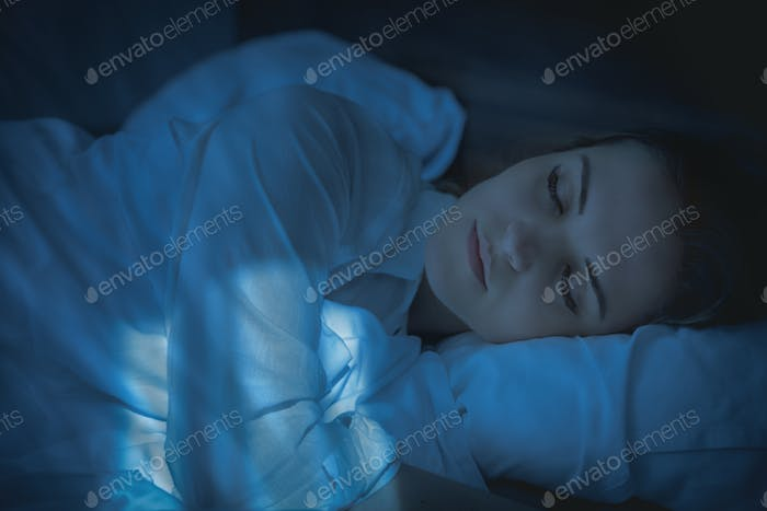 Pretty woman in bed peacefully sleeping at night