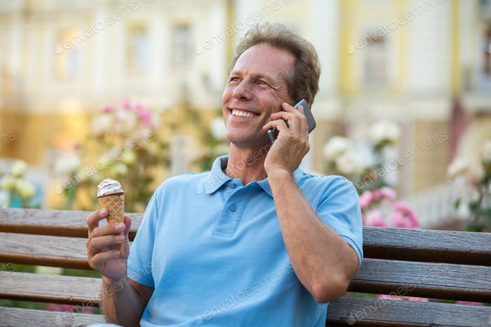 Mature man with phone smiling