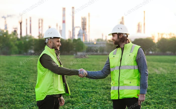 Two young engineers standing outdoors by oil refinery, shaking hands