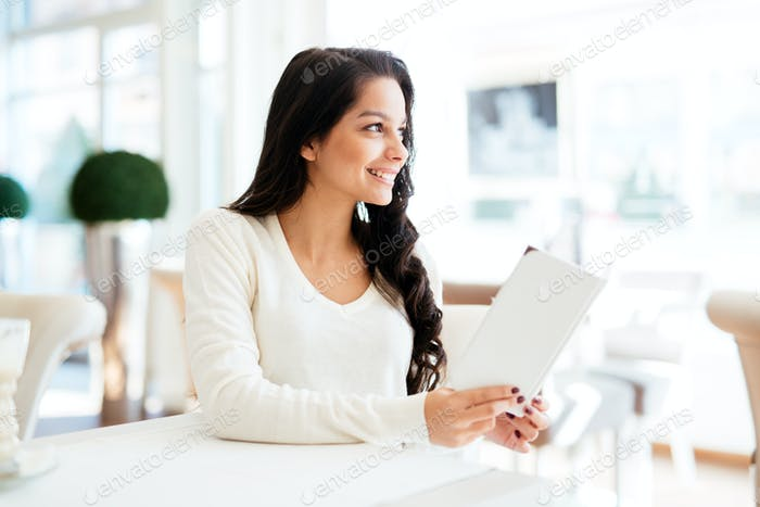 Beautiful woman looking at menu in modern restaurant