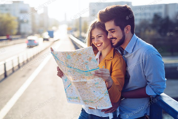 Happy tourist couple with map traveling outdoors