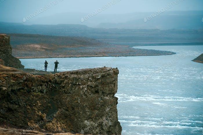 tourists on break rock  near river in fog