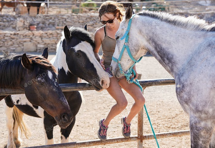Young woman cuddle with horses at ranch - Human and animal love
