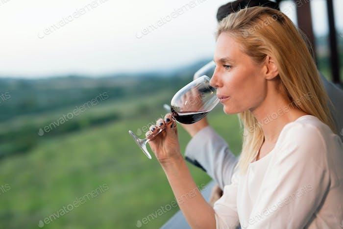 Woman tasting wine in wine grower vineyard