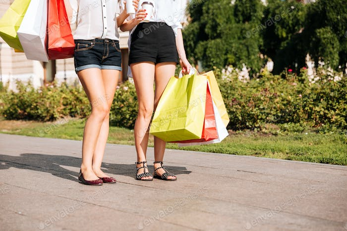 Two young female walking along street with shopping bags
