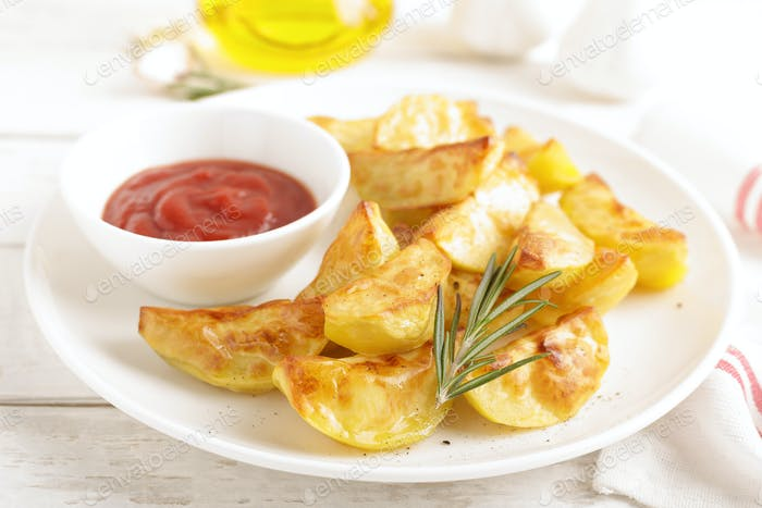 Potato baked and tomato ketchup on white plate, wooden background