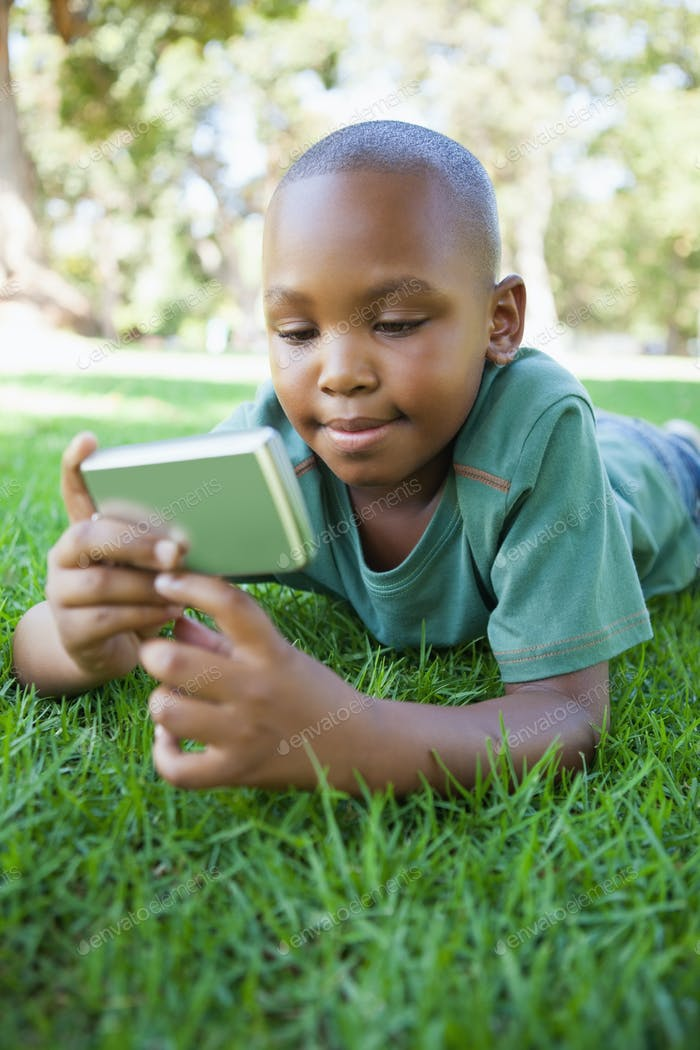 Little boy lying on grass looking at digital camera on a sunny day