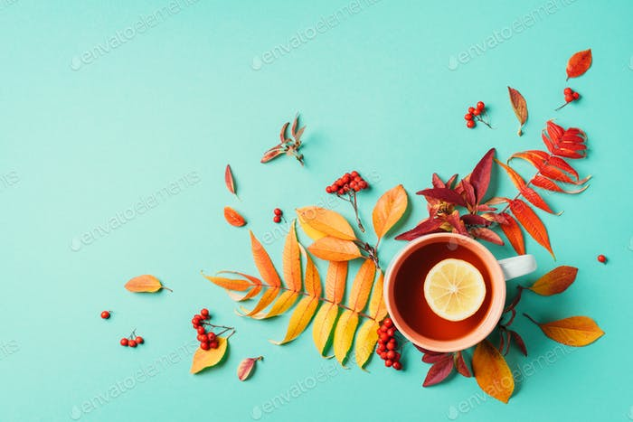 Autumn flat lay composition. Cup of tea, autumn bright leaves on blue background. Top view. Flat lay