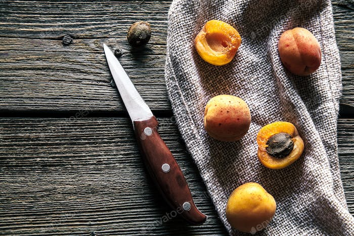 Fresh apricots with a knife on a kitchen towel. Wooden background. Fruit, food