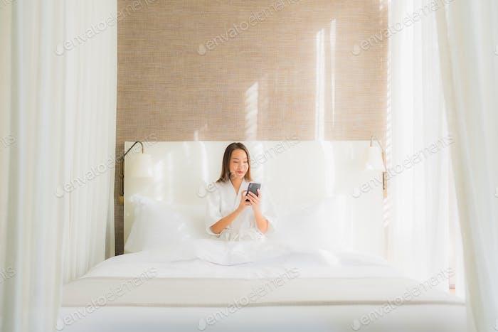 Retrato hermosa joven mujer asiática usando teléfono móvil inteligente en la cama en dormitorio