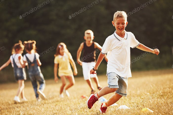 Through obstacles. Kids running in the field at sunny day. Conception of healthy lifestyle