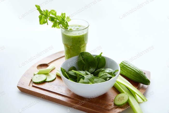 close up of glass with green juice and vegetables