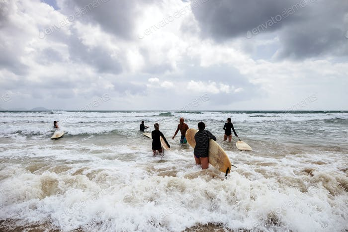 nicht identifizierte Frauen Surfer mit Surfbrettern kommen auf das Meer Rückansicht