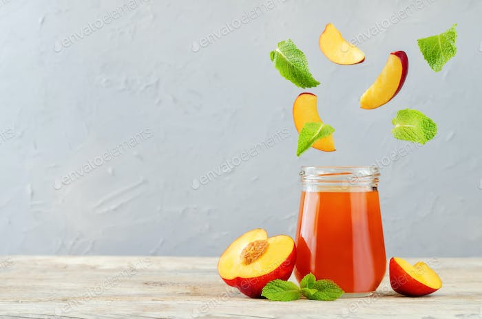 Peach jams with flying fresh peach slices and mint