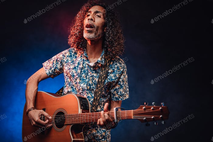 Hispanic musician emotionally singing and playing guitar on a dark illuminated by blue and red light