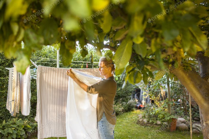 woman hanging laundry on clothesline in backyard