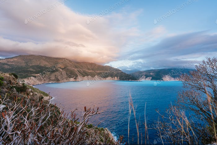 Kefalonia coastline, with rocky coast and dramatic sky on sunset. Greece vacation trip