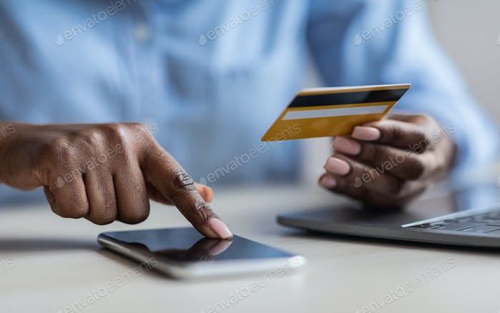 Unrecognizable Black Lady Browsding Mobile Banking App And Holding Credit Card