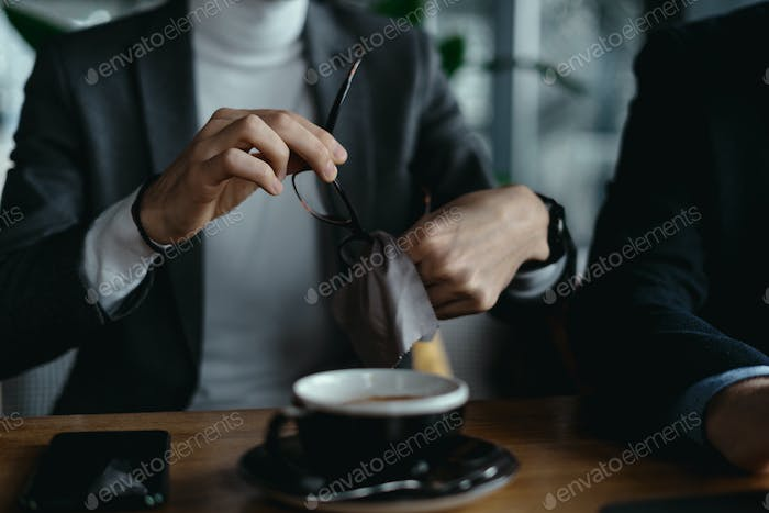 Business man cleaning his glasses with a cup of coffee