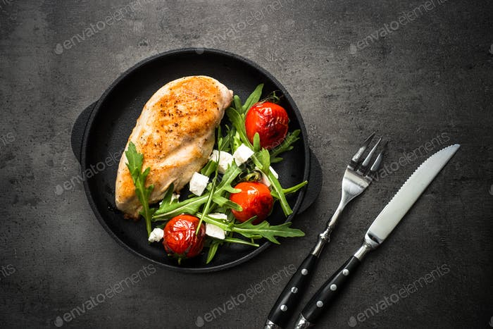 Grilled chiken fillet and fresh vegetables salad.