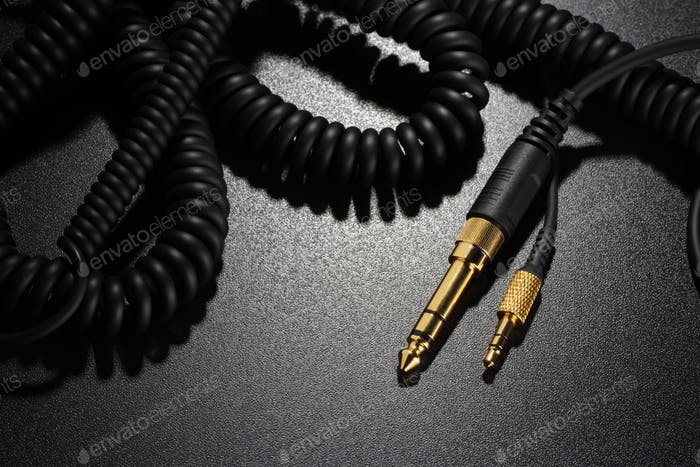 Jack connectors and audio cables on black background