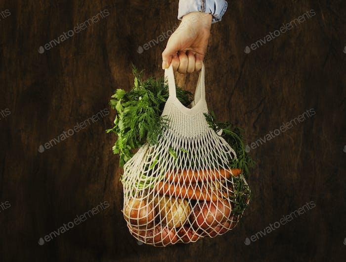 Bolsa de malla con verduras y hierbas en mano femenina. Bolsa de la compra de red con cadena para mujer