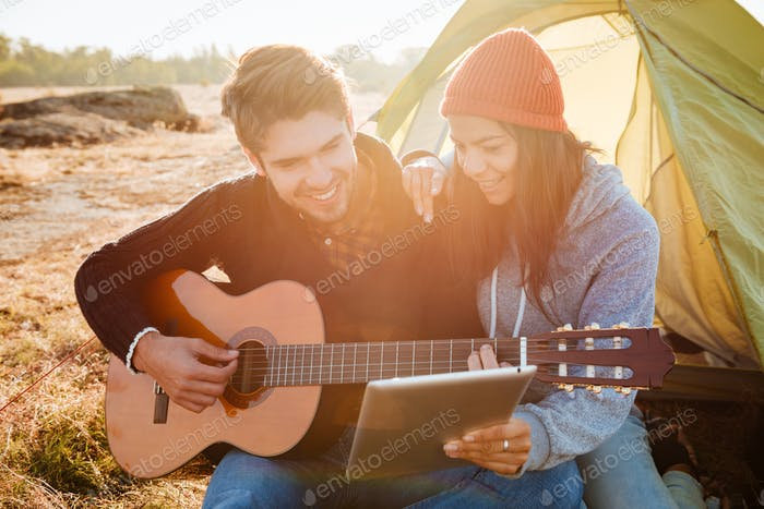 Happy couple with guitar near the tent