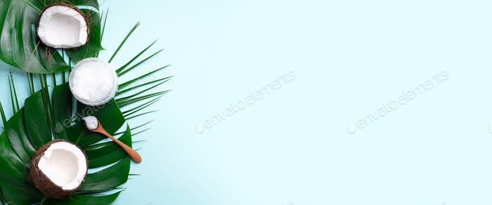 Tropical monstera leaves, ripe coconuts, coconut oil on blue background with copy space. Top view
