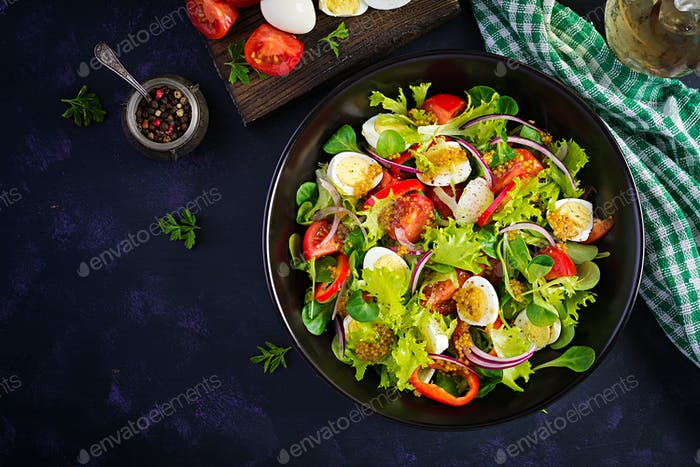 Fresh salad with vegetables tomatoes, red onions, lettuce and quail eggs
