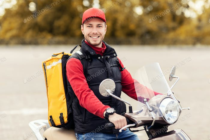Happy Delivery Man With Yellow Backpack Riding Moto Scooter Outdoors