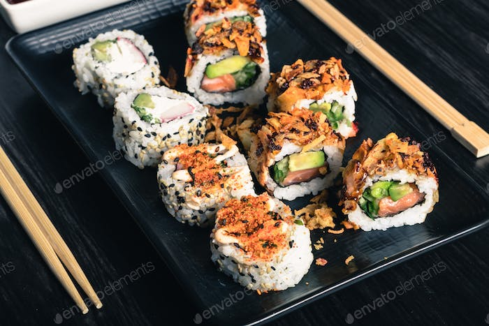 Sushi rolls with chopsticks and soy sauce on dark background