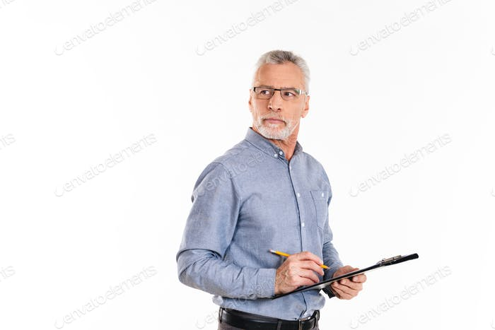 Serious confident man in glasses holding folder and looking away