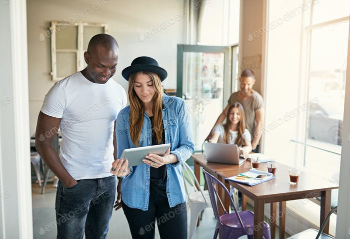 Young woman showing tablet to male co-worker