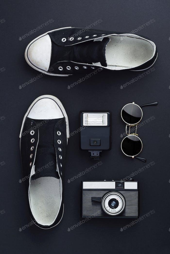 Zapatillas de deporte, cámara fotográfica, flash y gafas de sol redondas