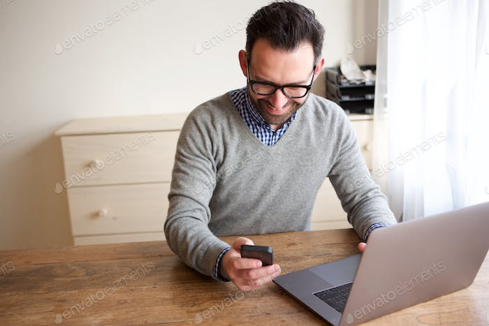 happy businessman working with laptop computer and looking at mobile phone